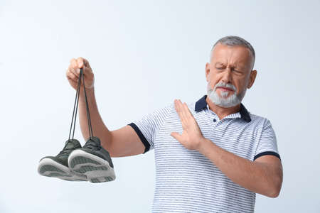 Man feeling bad smell from shoes on white background. Air freshener Stock Photo