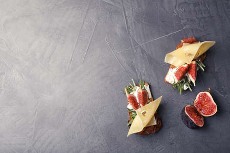 Sandwiches with ripe figs, prosciutto and cheese on grey background, top view. Space for text