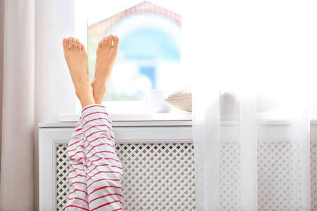 Woman warming up with feet on heater near window