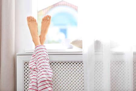 Woman warming up with feet on heater near window Stock Photo