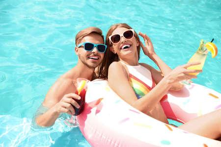 Pareja joven con cócteles en la piscina en un día soleado