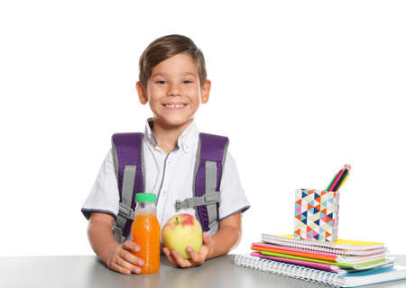Schoolboy with healthy food and backpack sitting at table on white background