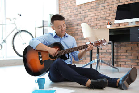 Glücklicher junger Geschäftsmann, der während der Büropause Gitarre spielt. Friedlicher Moment