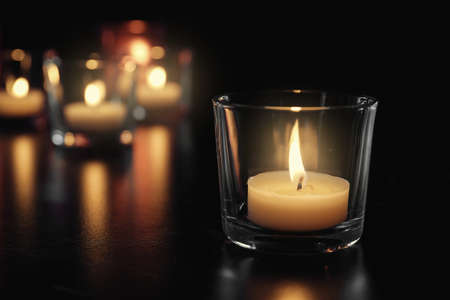 Burning candle on table in darkness, space for text. Funeral symbol Stock Photo