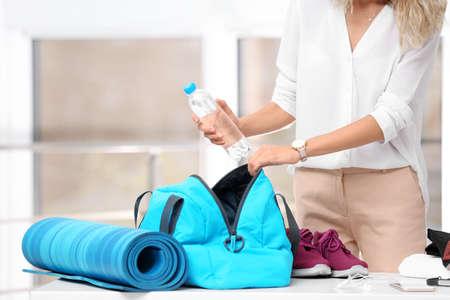 Junge Geschäftsfrau, die Sportartikel für das Training in Tasche im Büro packt Standard-Bild