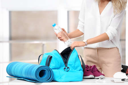 Young businesswoman packing sports stuff for training into bag in office Фото со стока