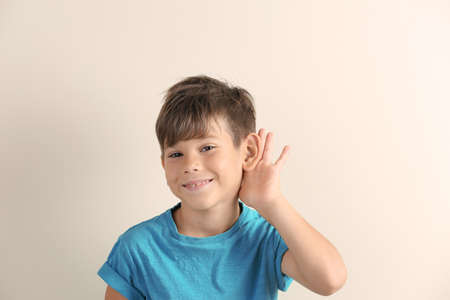 Cute little boy with hearing problem on light background