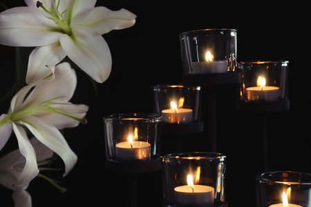 Burning candles and flowers on dark background. Funeral symbol