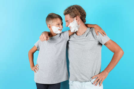 Father and son with shaving foam on faces against color background