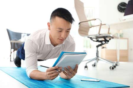 Junger Geschäftsmann macht Übungen im Büro. Fitness am Arbeitsplatz