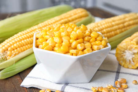 Bowl with corn kernels on wooden table 스톡 콘텐츠