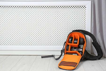 Bag with digital camera on floor indoors. Professional photographers equipment