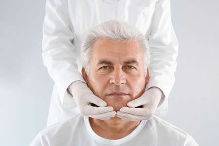 Doctor examining senior man face before cosmetic surgery on white background Imagens