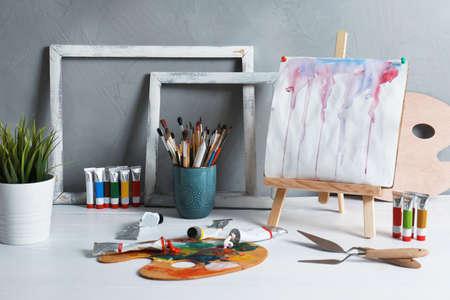 Chevalet avec peinture abstraite et ensemble de fournitures d'art professionnel sur table sur fond gris