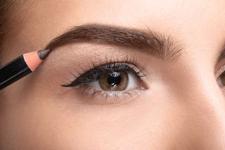 Young woman correcting shape of eyebrow with pencil, closeup