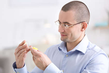 Young man with glasses holding contact lens case on blurred background