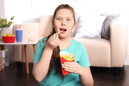 Overweight girl eating french fries indoors Imagens