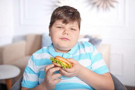 Übergewichtiger Junge mit Burger drinnen Standard-Bild