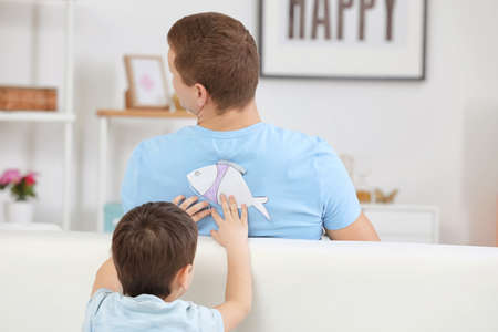 Little boy sticking paper fish to his father's back indoors. April fool's day prank