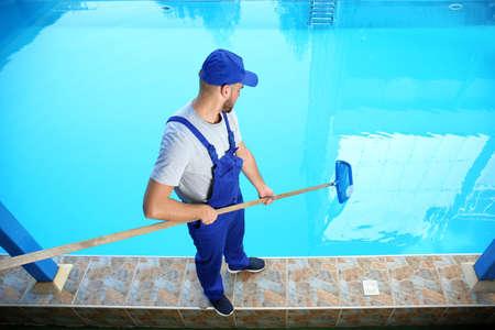 Männlicher Arbeiter, der Außenpool mit Schaufelnetz reinigt