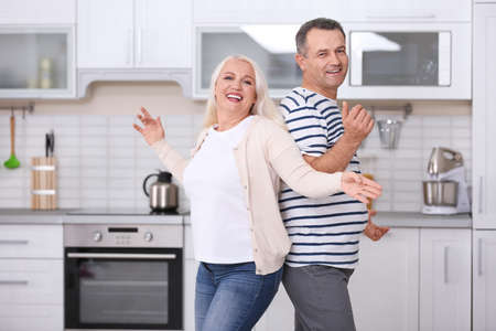 Happy mature couple dancing in kitchen Stock Photo
