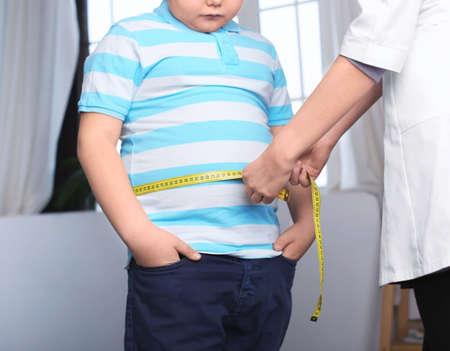 Docteur mesurant un garçon en surpoids en clinique Banque d'images