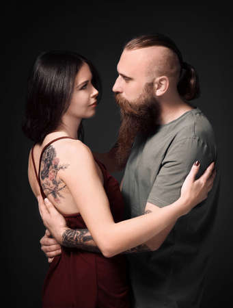 Attractive young couple with tattoos on dark background