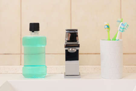 Mouthwash and holder with toothbrushes on sink in bathroom. Teeth and oral care Stock Photo
