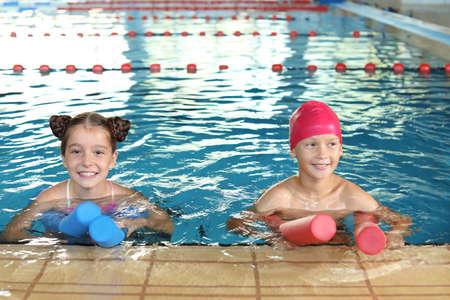Bambini piccoli con spaghetti di nuoto nella piscina coperta
