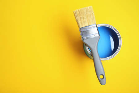 Paint can and brush on yellow background, top view. Space for text
