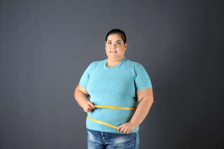 Overweight woman with measuring tape on gray background