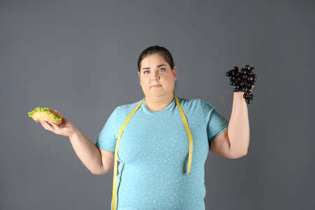 Overweight woman with hamburger, grapes and measuring tape on gray background