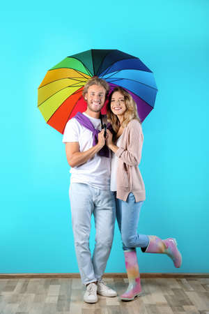 Couple with rainbow umbrella near color wall Banque d'images