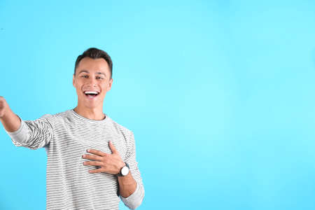 Laughing man taking selfie on color background. Space for text Imagens