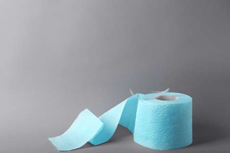 Roll of toilet paper with feather on grey background. Space for text