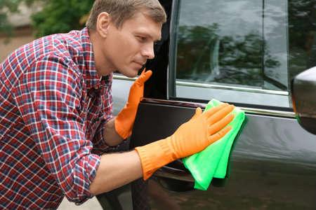 Man washing car door with rag outdoors