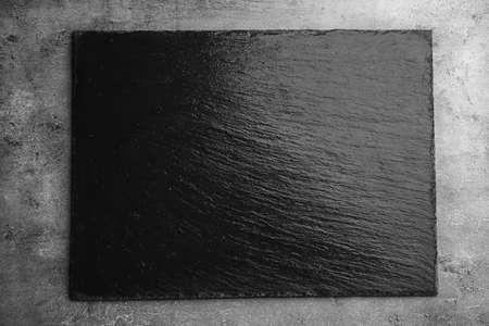 Black textured slate board on dark background Stock fotó