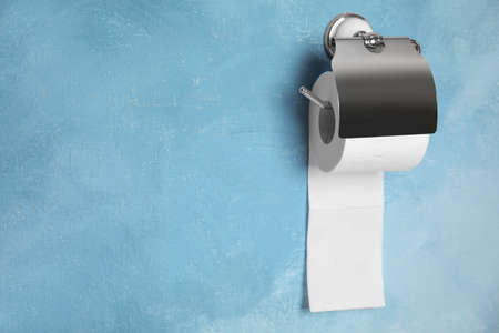 Toilet paper holder with roll on color background. Space for text Stock Photo