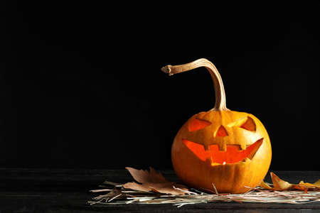 Halloween pumpkin head jack lantern on table against dark background with space for text