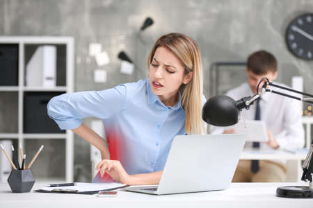 Young woman suffering from back pain at table in office Standard-Bild