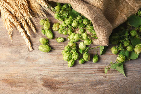 Fresh green hops and wheat spikes on wooden background, top view with space for text. Beer production Stockfoto - 109321002