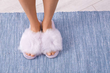 Woman in fuzzy slippers on carpet, closeup view with space for text. Floor heating