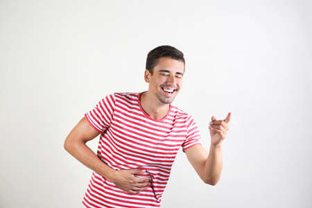 Portrait of handsome young man laughing on white background