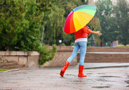 Young woman with bright umbrella under rain outdoors Banque d'images
