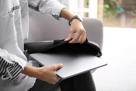 Woman putting laptop into case indoors, closeup
