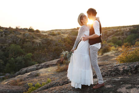Happy newlyweds with beautiful field bouquet standing on rock at sunset Banco de Imagens - 110014490
