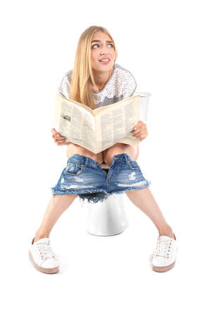 Young woman reading newspaper while sitting on toilet bowl. Isolated on white