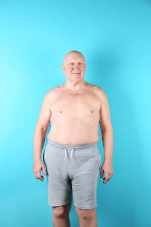 Fat senior man on color background. Weight loss