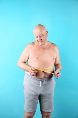 Fat senior man with measuring tape on color background. Weight loss Stock Photo