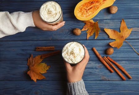 Women holding glasses with pumpkin spice latte on wooden background, top view